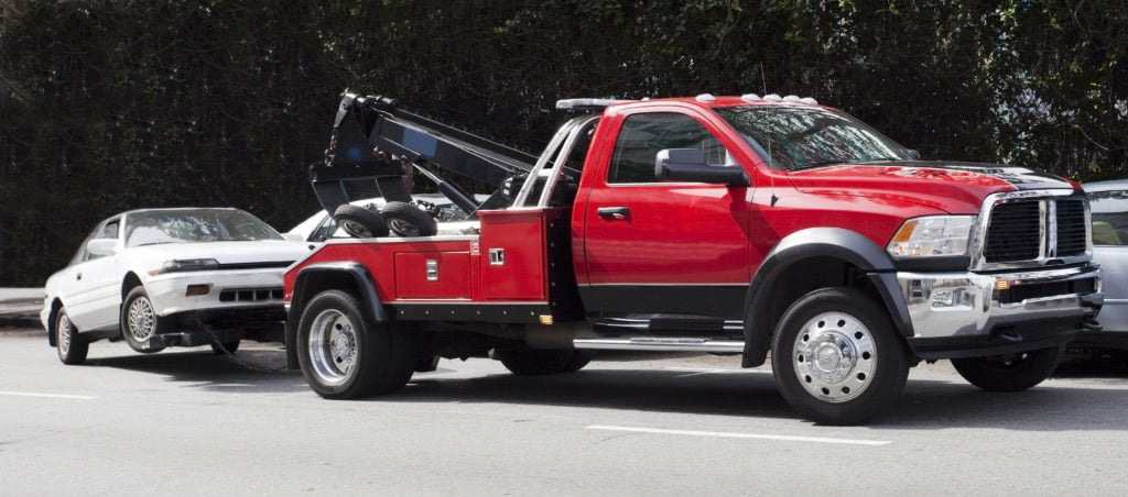 Red truck towing a small white car